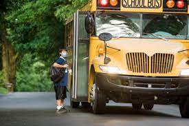 Student in mask boarding a School Bus.